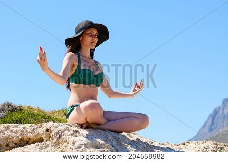 Young Attractive Woman Meditates Sitting On The Mountain
