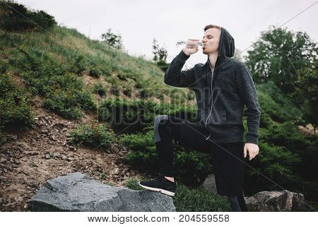 A young runner decided to have a short break after running a long distance and drink some water. He is really thursty.