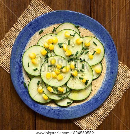 Fresh cucumber and corn salad with chives served on plate photographed overhead on dark wood with natural light