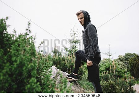 A well built guy is standing on the stone with the right leg and having some rest after a big running distance. he is analyzing his path and trying to make concequences from it.
