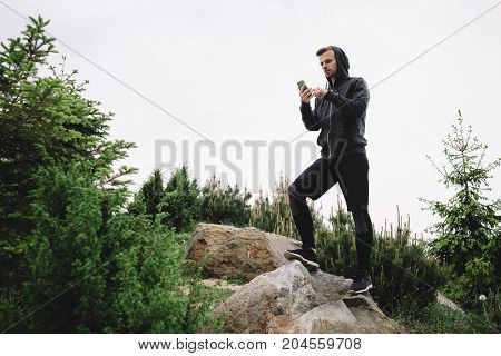 A young and powerful runner is standing almost at the top of hill and liikung to the phone's screen. He is probably checking his email or trying to call somebody. This guy look very serious and concentrated on what he is doing.