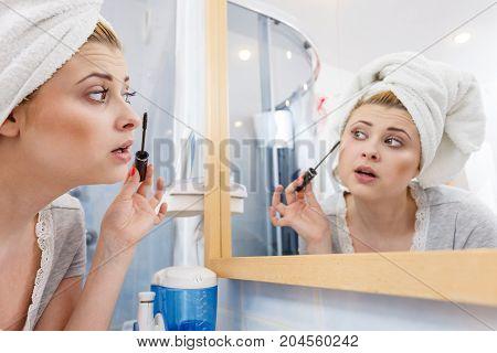 Woman In Bathroom Applying Mascara On Eyelashes