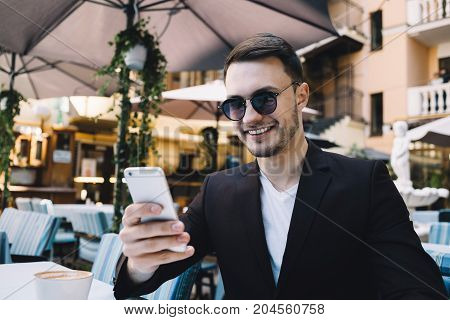Professional and successful businessman is sitting at the table in restaurant. He has his glasses on and looking to the phone's screen. Apparently he has a Skype call or checking his social media's profile because he is smiling. Close up. Cut view