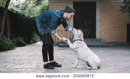 Very cute picture of a guy standing in front of the dog. He is holding the pet's paw in his right hd and stroking on the animal's head with left hand. This scene is very touchable and incredible.