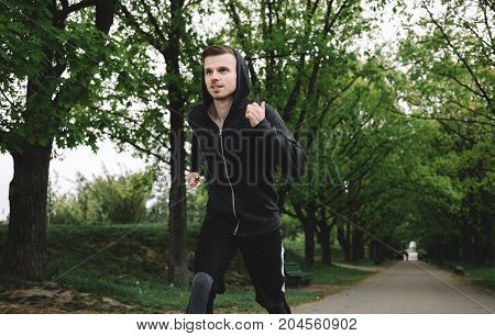 Well-built athletist is running on the road in the beautiful park. He is trying to run as fast as he can to beat up his previous record.