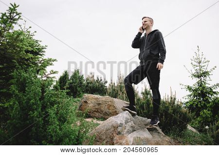 A picture of a runner standing near the top of a hill and talking on the phone. He is doing that during the short time for rest. He is smiling and enjoying the conversation.