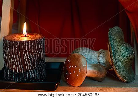 Candle and mushrooms under stairs and red fone