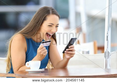 Excited on line buyer paying with credit card using a smart phone sitting in a bar terrace