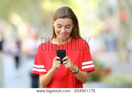 Front View Of A Teen Using A Smart Phone