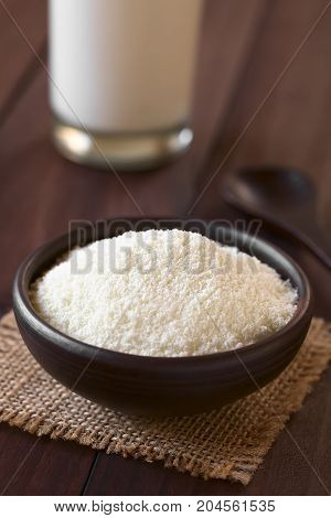 Powdered or dried milk in small bowl photographed on dark wood with natural light (Selective Focus Focus one third into the milk powder)