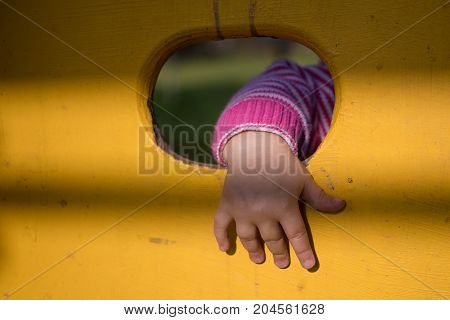 child's hand in a hole on playground
