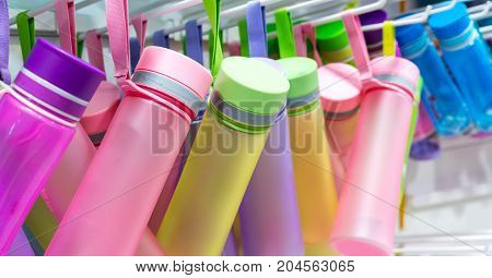 Rows Of Colorful Drink Bottles With Fabric Hand Strap Handing On Rack.
