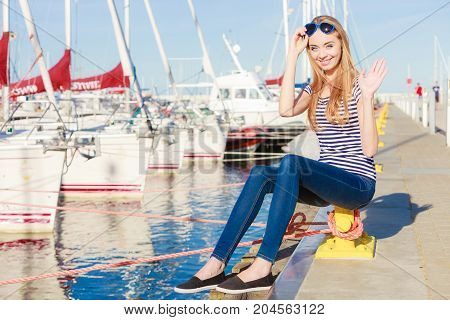 Travel tourism and people concept. Fashion blonde girl with blue heart shaped sunglasses in marina against yachts in port
