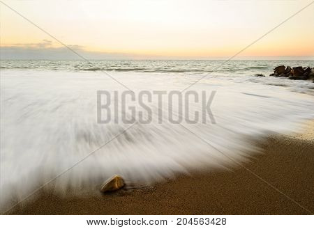 Nature abstract ocean sunset is a beach scene with a captured in time wave rushing to the shore.