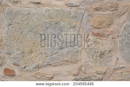 Big uneven stone in an ancient laying of a wall