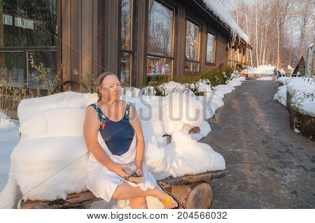 Senior healthy woman relaxing in winter spa outdoor. Healthy treatment. Winter.