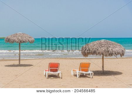 Idyllic sand beach with beach umbrella and beach chairs. Caribbean Sea. Cuba