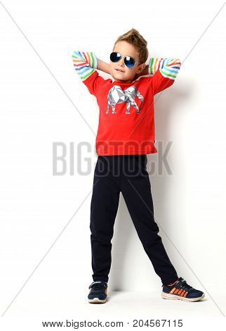 Happy young boy standing in light red shirt looking at the corner in sunglasses positive attitude, full lenght on white background