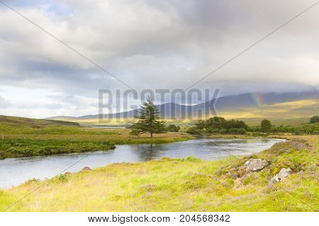 Scottish highland panorama with river and rainbow
