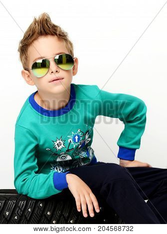 Happy young boy sitting in green sweater in aviator sunglasses positive attitude on white background