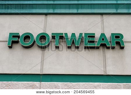 Footwear sign displayed outdoors for fashion information and directions.