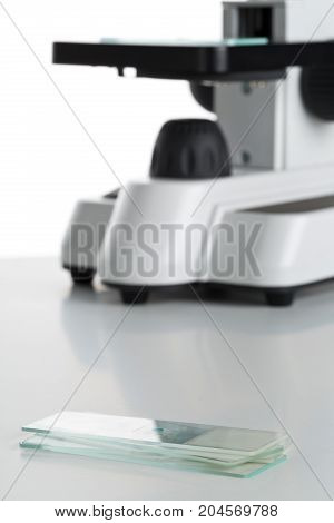 Stack of specimen holders in front of microscope over white background