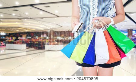 Woman Holding Shopping Bag And Credit Card In Shopping Mall