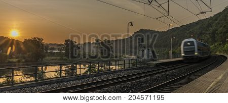 Electric double deck train with sunrise in Uholicky village