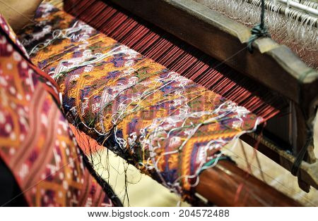 A traditional hand-weaving loom being used to make Thai silk cloth, Thailand Household handicrafts of Thai silk