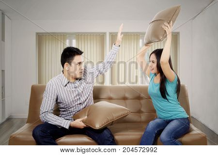 Picture of young woman quarrel her husband while sitting on the couch. Shot at home