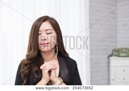 Closeup on a young asian woman pray believe concept