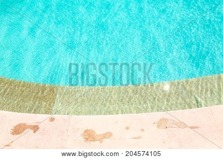 Wet foot prints on side of turquoise swimming pool