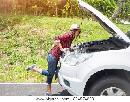 Woman leaning over checking her car engine after breaking down in the roadside.