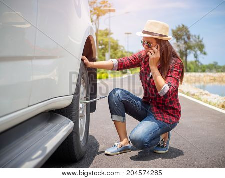 Sad woman could not remove the wheel. Calling on the phone to the garage and asks for help in repairs.