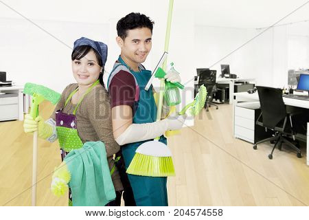 Picture of cheerful young janitors holding cleaning equipment while standing in the office