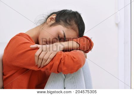 Young Asian Woman Sitting On The Floor And Feeling Tired