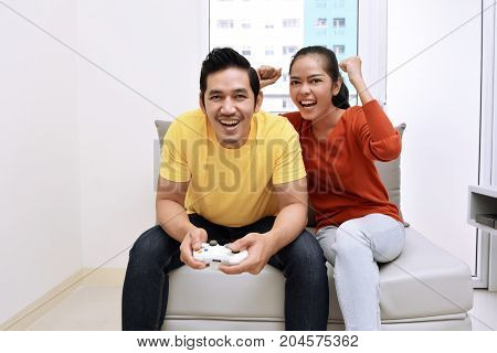 Happy Asian Couple Sitting On Couch And Playing Video Games