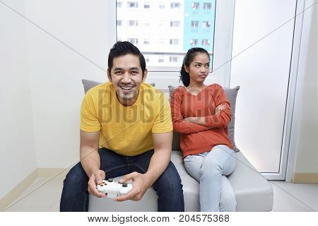 Portrait Of Bored Asian Woman While Her Boyfriend Playing Video Games