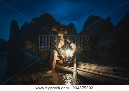 Guilin China : June 17th 2014 - Shot of the famous Guilin's cormorant fishreman preparing his lantern for night fishing.