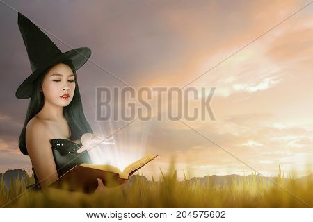 Beautiful asian witch woman with hat learning magic from the book over dramatic sky background