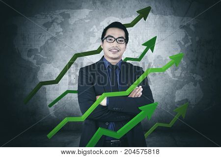 Picture of confident businessman smiling at the camera while standing with arrows upward of finance statistic
