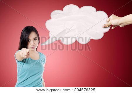 Portrait of young woman looks angry while pointing at the camera with an empty cloud bubble