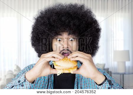 Image of Afro man looks excited while eating a big cheeseburger in the living room