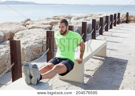 Portrait of content young strong handsome man wearing sportswear and doing triceps dips on concrete benches with sea in background
