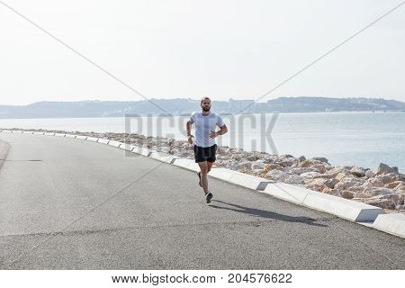 Determined young strong man wearing sportswear and running on seaside road with sea in background