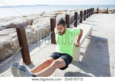 Portrait of content young strong handsome man wearing sportswear and doing triceps dips on concrete benches with sea in background. High angle view.