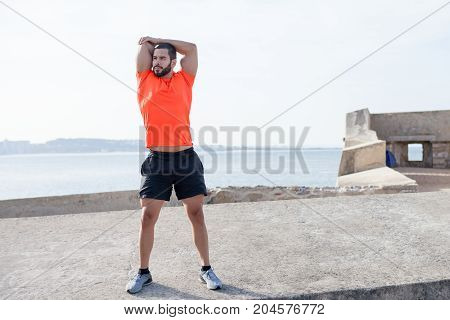 Serious young handsome strong man wearing sportswear, standing on concrete platform and stretching arm with river in background. Front view.