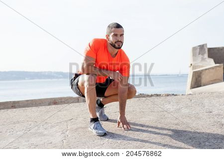 Portrait of pensive young handsome strong man wearing sportswear, looking away and sitting on hunkers with river in background