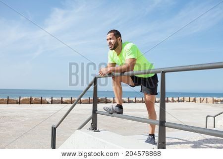 Portrait of young handsome strong man wearing sportswear, looking away, relaxing and leaning on railing at seaside