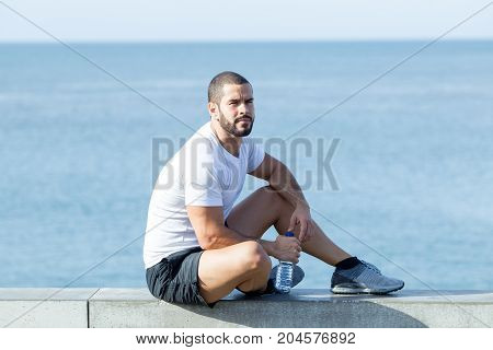 Portrait of pensive young handsome strong man wearing sportswear, looking away, holding bottle of water and sitting on parapet. Side view.